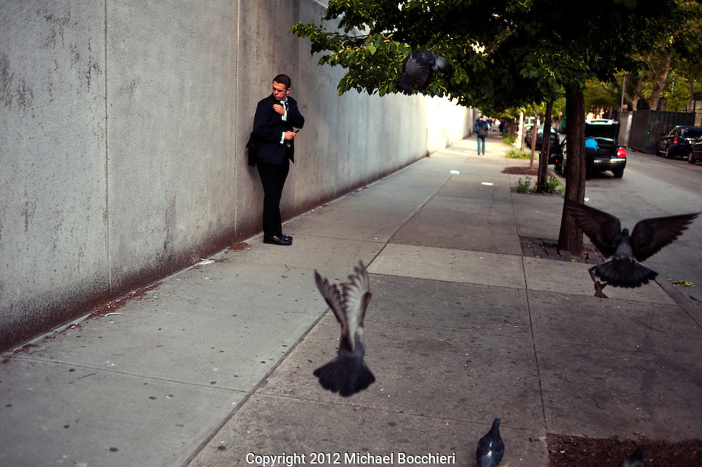 NEW YORK, NY - May 10:  A man checks his coat as pigeons fly on May 10, 2012 in NEW YORK, NY.  (Photo by Michael Bocchieri/Bocchieri Archive)