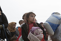 Licensed to London News Pictures. 10/11/2016. Mosul, Iraq. A young girl looks west towards the centre of Mosul as she and other families, escaping from areas within the city where fighting between Iraqi Security Forces and Islamic State militants is taking place, stand in line as they wait to board a bus in the city's Gogjali District. The bus, provided by the Iraqi Army, will take them to the safety of a refugee camp in Iraqi-Kurdistan.<br /> <br /> The battle to retake Mosul, which fell June 2014, started on the 16th of October 2016 with Iraqi Security Forces eventually reaching the city on the 1st of November. Since then elements of the Iraq Army and Police have succeeded in pushing into the city and retaking several neighbourhoods allowing civilians living there to be evacuated - though many more remain trapped within Mosul. Photo credit: Matt Cetti-Roberts/LNP