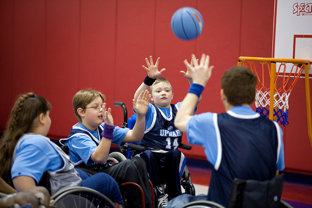"""Kellogg Foundation Assignment: Wheelchair Basketball..Conner Riffenhouse raises his hands to catch a pass made by his teammate...The contact is Pam Patula, 888/957-6245 runs an organization.called Socil (S.E. center for Independent Living )a member of April.  A weekly wheelchair basketball game in Lancaster, held on Jan 20th. Saturday at 10am. The basketball coach, Brett Harbage, is an Independent Living Specialist from SOCIL.  Other coach is Cheryl """"Hutch"""" Hutchinson, she is the adaptive physical education instructor of Fairfield County.  The adaptive basketball games are part of the Upward Basketball league, .  This is only Upwards adaptive league in the nation."""
