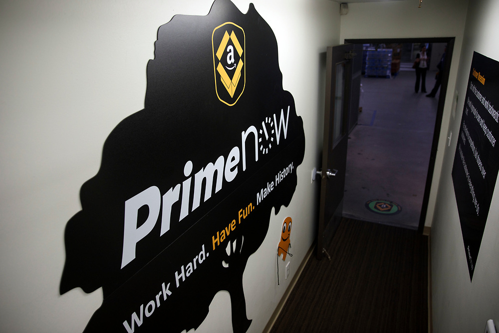 The Amazon.com Prime Now logo is displayed on a wall at the Amazon.com Inc. Prime Now fulfillment center warehouse on Monday, March 27, 2017 in Los Angeles, Calif. The warehouse can fulfill one and two hour delivery to customers. Complex supply chains such as Amazon's and e-commerce trends will impact city infrastructure and how things move through cities. © 2017 Patrick T. Fallon