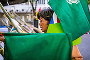 "11 MAY 2013 - BANGKOK, THAILAND:  A Thai protesters picks up the green flags of the P-Move organization. Several hundred small scale family farmers camped out ""Government House"" (the office of the Prime Minister) in Bangkok to Thai Prime Minister Yingluck Shinawatra to deliver on her promises to improve the situation of family farmers. The People's Movement for a Just Society (P-move) is a network organization which aims strengthen the voices of different, but related causes working to bring justice for marginalized groups in Thailand, including land rights for small-scale farmers, citizenship for stateless persons, fair compensation for communities forced to relocate to accommodate large scale state projects, and housing solutions for urban slum dwellers, among others.   PHOTO BY JACK KURTZ"