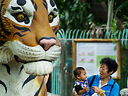 17 AUGUST 2018 - BANGKOK, THAILAND:   A woman and child in front of a cement statue of a tiger in the predator display at Dusit Zoo in Bangkok. The zoo opened in 1938. The zoo grounds were originally the Dusit Royal Garden. The zoo is scheduled to close by the end of August 2018 because it is being relocated to Nakhon Pathom province, south of Bangkok.      PHOTO BY JACK KURTZ