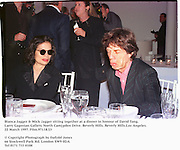 Bianca Jagger & Mick Jagger sitting together at a dinner in honour of David Tang. Larry Gagosian Gallery. North Cam[pden Drive. Beverly Hills. Beverly Hills.Los Angeles. 22 March 1997. Film.97118/23<br />