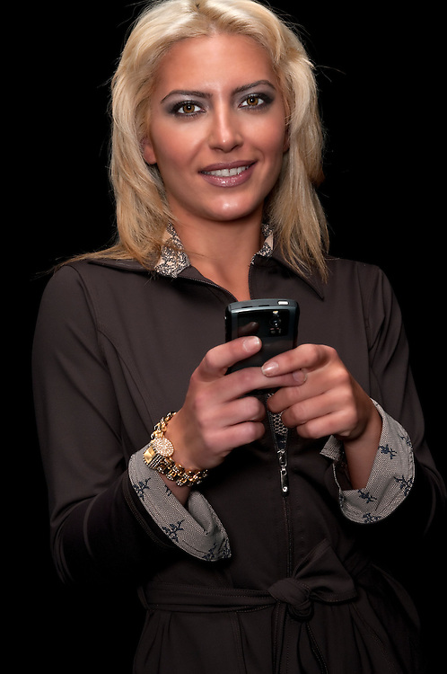Young woman sending text message or email from pda.