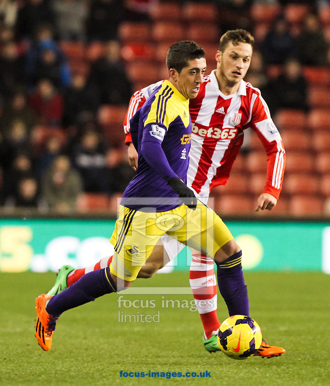 Marko Arnautović (right) of Stoke City is left behind by Pablo Hern&aacute;ndez (left) of Swansea City during the Barclays Premier League match at the Britannia Stadium, Stoke-on-Trent<br /> Picture by Tom Smith/Focus Images Ltd 07545141164<br /> 12/02/2014
