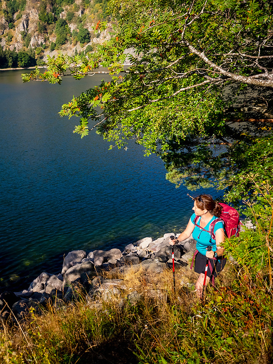 Women hiker passing by lakeside at Lac Blanc, France
