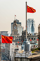 Shanghai, China - April 7, 2013: the bund rooftops and chineses flags at the city of Shanghai in China on april 7th, 2013