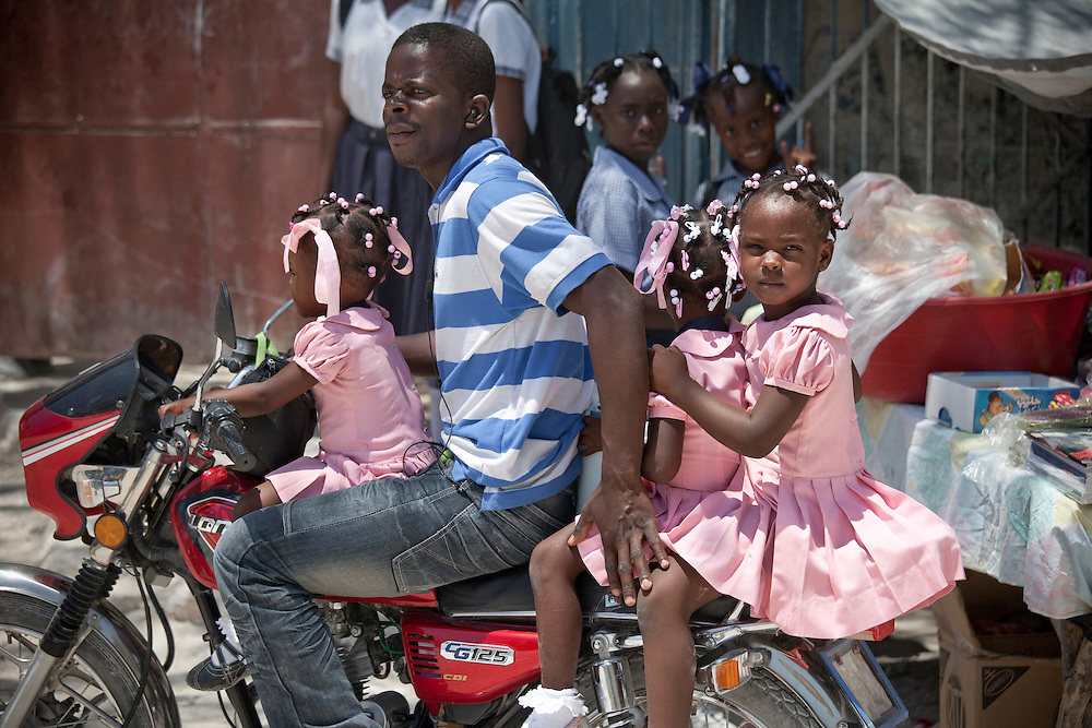 A man gives three schoolgirls a ride home from school on his motorbike in Anse a Galat, Ile de la Gonave, Haiti