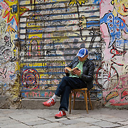 Man reading book in front of graffiti covered wall on neighborhood street Via dello Orologio, Palermo, Sicily, Italy