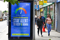 © Licensed to London News Pictures. 22/05/2020. London, UK. People walk past a 'CORONAVIRUS - STAY ALERT TO KEEP R DOWN' digital poster in north London, which is a part of the government's new public information campaign as the lockdown is eased. Photo credit: Dinendra Haria/LNP