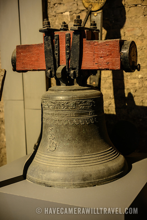 A bell on display in an exhibit on the hsitory of the carillon in the Belfry of Bruges. The Belfry (or Belfort) is a medieval bell tower standing above the Markt in the historic center of Bruges. The first stage was built in 1240, with further stages on top built in the late 15th century. The Carillon consists of 47 bells. 26 bells were cast by Georgius Dumery between 1742 and 1748 and 21 bells were cast by Koninklike Eijsbouts in 2010. The bourdon weights 6 tons, and the bells have a combined weight of 27 tons.