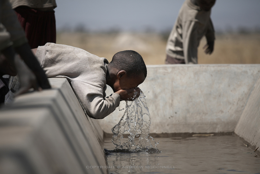 A boy washes the dust from his face in a cattle trough in Tedecha Guracha, Ethiopia.