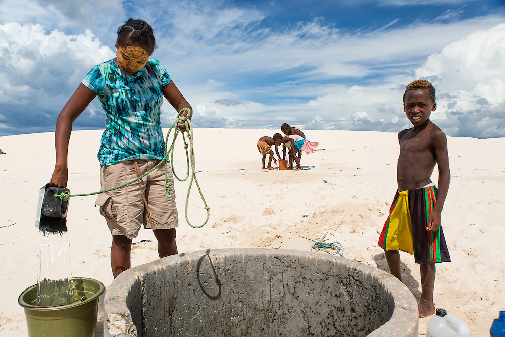 A Vezo women collects clean water from a well in the sand near a village of traditional fishers in south west Madagascar.  Many villages do not have proper wells and fetching clean drinking water is a time-consuming task that women must undertake each day.   Each drop is carefully used. The rural people of coastal south west Madagascar lead fragile lives in a natural environment that is both arid but that can also experience violent cyclones from December to March.  At the same time they depend on coral reef fisheries for food and income.  This makes them among the most vulnerable coastal people to climate change in the world.