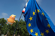 London, UK: The inflatable balloon called Baby Trump flies above the European Union flag in Parliament Square in Westminster, the seat of the UK Parliament, during the US President's visit to the UK, on 13th July 2018, in London, England. Baby Trump is a 20ft high orange blimp depicting the US President as an enraged, smartphone-clutching infant - and given special permission to appear above the capital by London Mayor Sadiq Khan because of its protest rather than artistic nature. It is the brainchild of Graphic designer Matt Bonner. Photo by Richard Baker / Alamy Live News