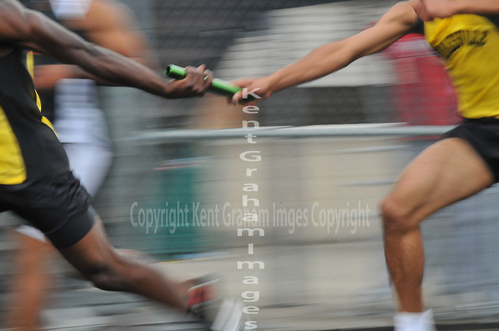 Runners exchange baton in 4x100 relay.