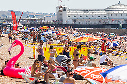 © Licensed to London News Pictures. 07/07/2016. Brighton, UK. Members of the public take the beach in Brighton and Hove as sunny and hot weather continues to hit the seaside resort. Photo credit: Hugo Michiels/LNP