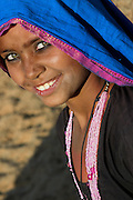 Smiling, happy gypsy girl who lives in the Thar desert of Rajasthan, India. She wears a 'dupatta', a traditional headscarf.