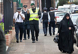 © Licensed to London News Pictures. 19/09/2018. London, UK. Police and a private security guard talk outside The Hussaini Association Islamic Centre in Cricklewood, north London where a car hit two pedestrians last night. The incident , which took place in the early hours of this morning outside the centre, is being treated as a possible hate crime. Police are looking for a male driver who failed to stop at the scene, as well as two men and one woman in the car, all in their 20s. Photo credit: Peter Macdiarmid/LNP