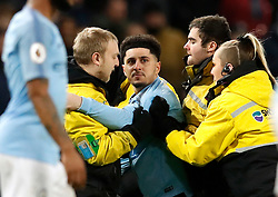A pitch invader is escorted off the pitch during the Premier League match at the Etihad Stadium, Manchester.