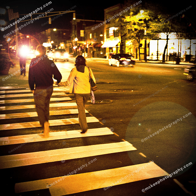 couple crossing a street, in cross walk, with lens flare