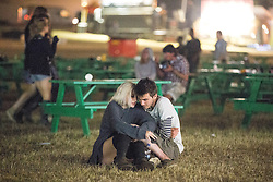 © Licensed to London News Pictures . 22/07/2013 . Suffolk , UK . Love amongst the ruins as a couple huddle together and kiss whilst around them the venue is cleared . Revellers enjoy the final night of the Latitude Festival . The Latitude music and culture festival in Henham Park , Southwold . Photo credit : Joel Goodman/LNP