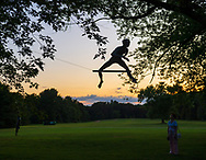 "Old Westbury, New York, U.S., September 1, 2019. ""Athlete 1 - Over the Hurdle"" seen silhouetted by sky at upper right, is one of 33 outdoor sculptures by Jerzy Kedziora (Jotka), b. 1947 in Poland, and his Balance in Nature art is on view at historic Old Westbury Gardens in Long Island, until October 20, 2019. Seen at dusk, the life-size, bronze resin balancing sculpture, is balanced on wire suspended from trees. Athlete III - Deep Plunge is seen dimly at lower left ground."