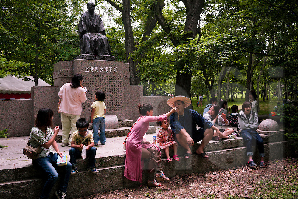 Japanese families sit around a statue surrounded by trees in a park in Japan, Asia