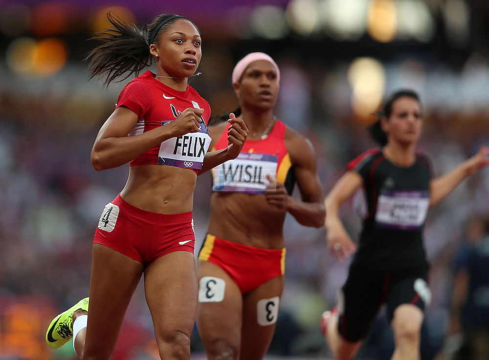 Allyson Felix of the USA (L) runs in a 100m heat during track and field at the Olympic Stadium during day 6 of the London Olympic Games in London, England, United Kingdom on August 3, 2012..(Jed Jacobsohn/for The New York Times)..