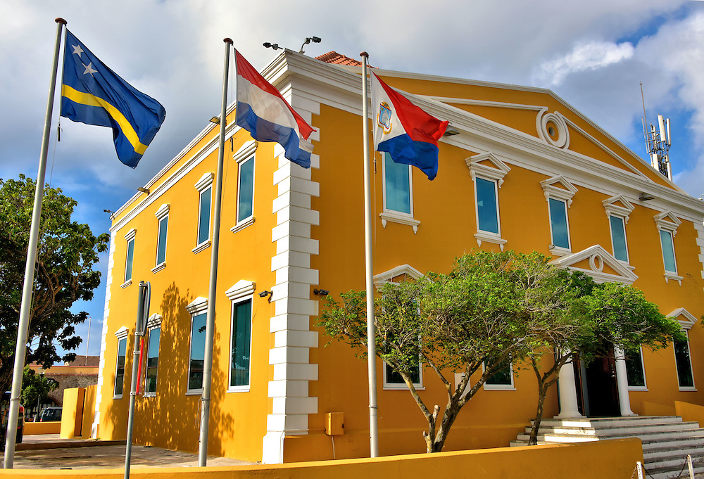 Attorney General Office in Punda, Eastside of Willemstad, Curaçao <br /> This yellow building began as the Masonic Lodge De Vergenoeging when it opened in 1869.  A century later it changed hands several times among various financial companies before becoming the Attorney General Office in 2011.  Notice the three flags. They are from left to right: Curaçao, the Netherlands and Sint Maarten. The Parket Procureur-General also provides public prosecution services to the BES Islands (Bonaire, Sint Eustatius and Saba).