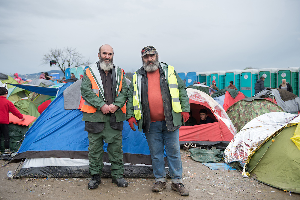 Andonis Abatzidis (R) and Felix Tsolakidis (L) both homeless from Thessaloniki working as cleaners in the transit camp of Idomeni, Greece. <br /> <br /> Thousands of refugees are stranded in Idomeni unable to cross the border. The facilities are stretched to the limit and the conditions are appalling.