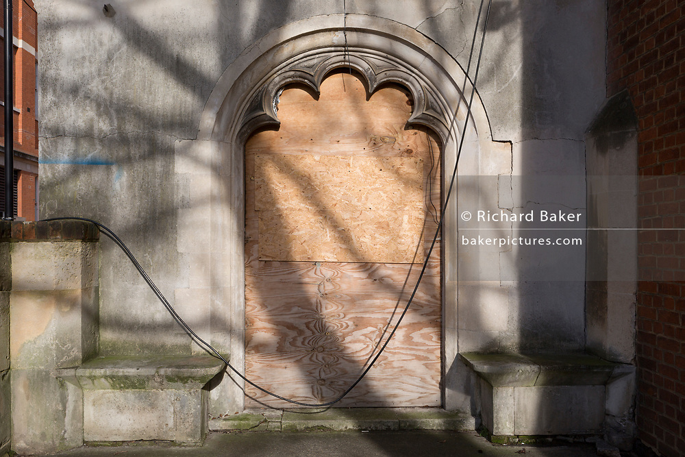 The shadows of tree branches across the boarded-up entrance of All Hallows, an inner-city church on Copperfield Street, on 30th January 2018, in the south London borough of Southwark, England. All Hallows Church Southwark was designed by George Gilbert Scott Junior and built in 1879-80 in Copperfield Street south of the river. The church suffered bomb damage on two occasions in WW2, in addition to being gutted by a landmine where it remained a relative ruin. It was not until 1957 that any attempt was made to salvage the bombed church, but due to the poor state of the surviving remains, the main structure and northern parts of the building had to be demolished.