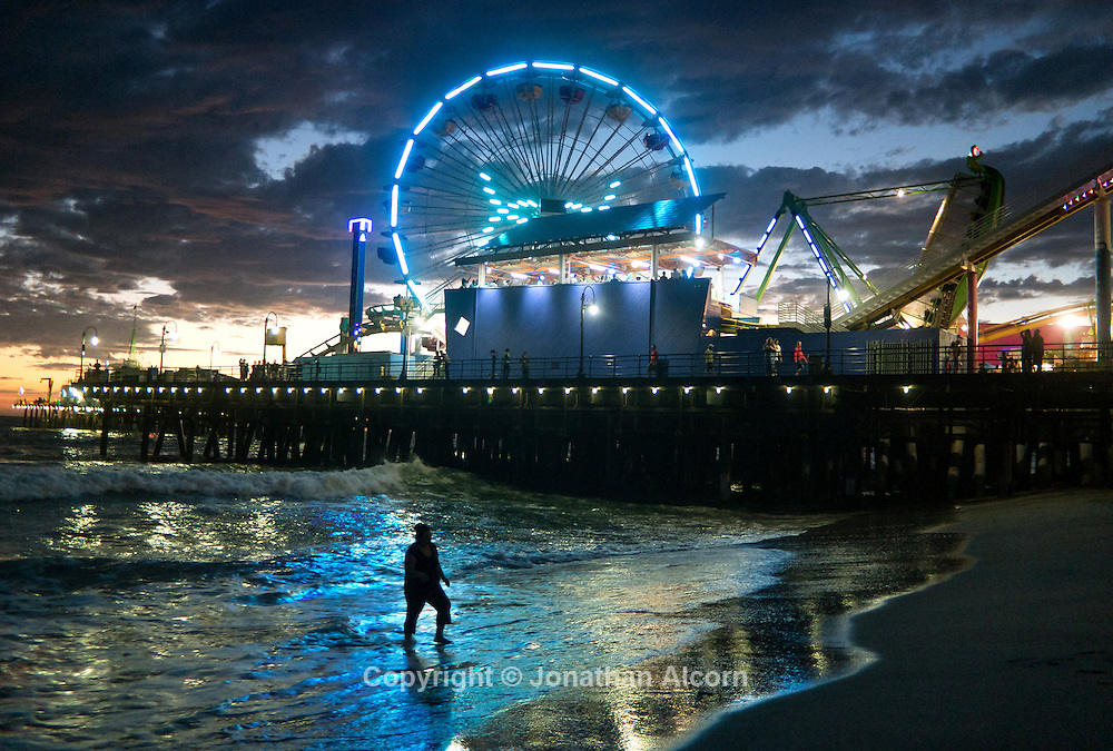 A woman walks in the ocean water next to the Santa Monica pier and the Pacific Ferris wheel