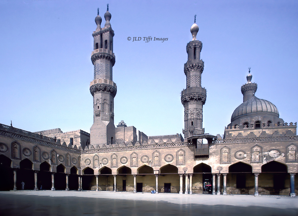 Courtyard of Al Azhar mosque, Cairo, seat of Al Azhar University.  Al Azhar was founded 970 AD as a theological college.  Today it includes faculties of agriculture, medicine, and law. This image was made in 1979.  The huge courtyard is empty except for a student seated bent over in study under the arcade.