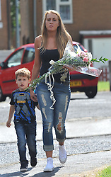 © London News Pictures. 29/07/2013. Manchester, UK. A member of the public laying flowers with her boy at  the scene on Delta Walk, in Moston, Manchester where A father has been stabbed to death and his 13-year-old child left in a critical condition. A second man, who also suffered stab wounds,  died after he crashed a hijacked car into a nearby pub. Photo credit Steve Allen/LNP