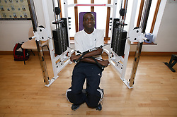 Access to services, Disabled man in the gym; using arm strengthening equipment,