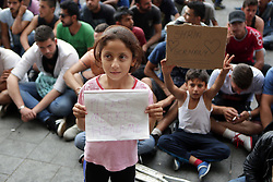 © Licensed to London News Pictures. Young refugees, who did not board trains, hold up signs inside Keleti train station in Budapest, Hungary on 3rd of September, 2015. Earlier in the day groups of migrants where transported to camps unaware of where they were being taken. Photo credit: Gabriel Szabo/LNP