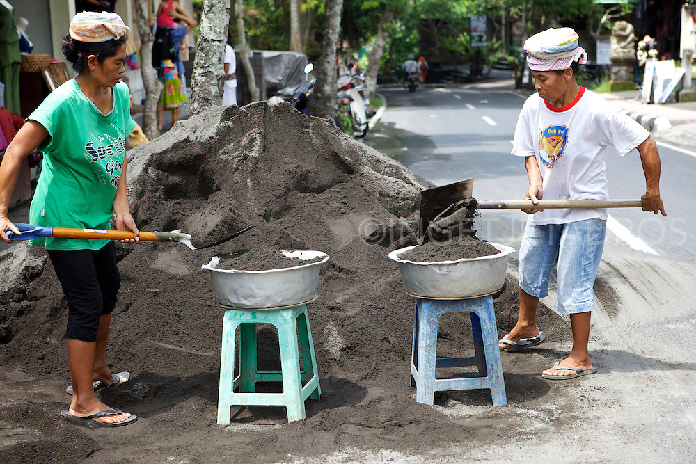 Balinese women labouring on a street, filling and carrying heavy baskets of sand. &copy;Ingetje Tadros<br /> www.ingetjetadros.com