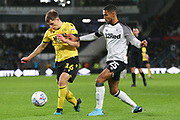 Millwall midfielder Jayson Molumby (16) is challenged by Derby County defender Max Lowe (25) during the EFL Sky Bet Championship match between Derby County and Millwall at the Pride Park, Derby, England on 14 December 2019.