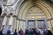 Tourists and visitors queue patiently beneath Gothic arches at the eastern entrance to Westminster Abbey, London.