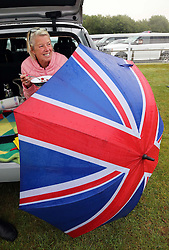 A race goer has her picnic lunch from the back of her car during at a wet and windy opening day of Glorious Goodwood in the UK, Tuesday, 30th July 2013 <br /> Picture by Stephen Lock / i-Images