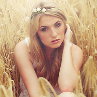 Young woman sitting in a field wearing a white top and flowers in the hair and looking thoughtfully in the camera