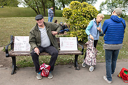 """© Licensed to London News Pictures. 16/05/2020. Manchester, UK. A man sits on a bench alongside placards reading """" No mandatory vaccines """" , """" Beware Poison """" """" No 5G """" and """" Hey Bill Gates Fuck you and your vaccine """" . An anti-lockdown, """"mass gathering"""" demonstration is held in Platt Fields Park in protest at government measures to control the spread of Covid-19. A group calling itself the UK Freedom Movement has organised a series of demonstrations across the UK. Photo credit: Joel Goodman/LNP"""
