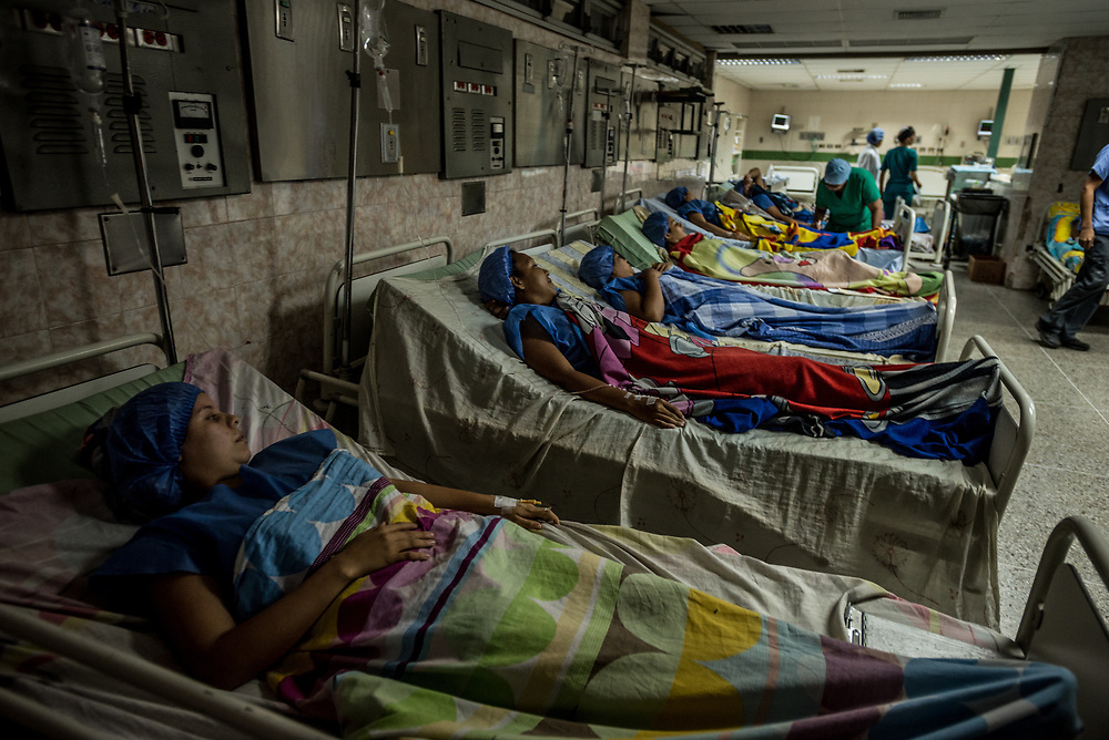 "CARACAS, VENEZUELA - JULY 8, 2017: Twenty-one women wait to be surgically sterilized during a free sterilization event at the public, and government-run José Gregorio Hernández​ Hospital in the working-class neighborhood of Catia. The hospital has sterilized over 300 women through this program. The women being operated on this day ranged in age from 25 to 32 years old, all 21 have multiple children, and expressed wanting to get sterilized because the economic crisis in Venezuela has made it too difficult to raise children. They all said they feared becoming pregnant again. The economic crisis has led to widespread shortages of essential baby supplies, like diapers, formulas, milk and medicine.  It was also led to widespread shortages of birth control pills and condoms - many mothers at sterilization event said their most recent pregnancies had been unplanned and unwanted and happened because they did not have access to birth control - so they opted for sterilization as a guaranteed way to not get pregnant again. One of the women getting sterilized during the clinic this day was professional hair stylist, Eddy Farías, 25, who is a single mother of five children. Her wages as a full-time employee at a hair salon are barely enough to feed her children -  so she decided to get sterilized to prevent from getting pregnant again.  ""It's hard to be a mom, it's hard! she said. ""You cannot find anything…if your child gets sick, you have to run circles trying to find a hospital [to admit them],"" she said.  ""It is a war just to survive day to day.""  After her operation, she was in pain from the large incision made across her lower abdomen - but said she felt relieved that she would no longer have to jump through the hoops Venezuelan mothers must jump through to access the basic supplies needed to raise a child. ""If I got pregnant again, that would mean I'd have to go to war again for diapers…it is like war to have to buy diapers on the black market, or have t"