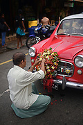 Man decorates wedding car with flowers, Galle, Sri Lanka