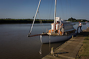 Yacht crew cleaning decks on the River Yare at Reedham on the Norfolk Broads.