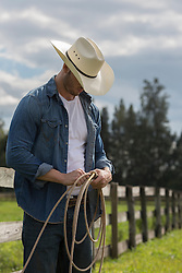 hot cowboy holding a lasso outdoors on a ranch