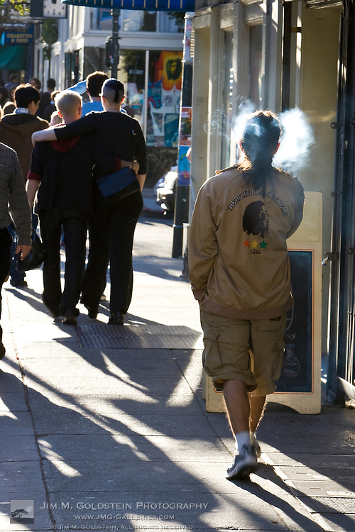 A young man wearing a Reggae jacket smokes as he walkes down Haight street in San Francisco
