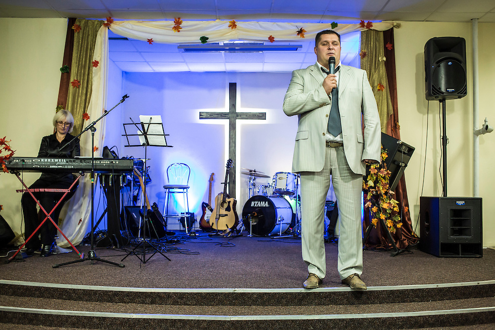 DNIPROPETROVSK, UKRAINE - OCTOBER 12: Volodymyr Ivanov, pastor at the Good News Evangelical Church, leads a service on October 12, 2014 in Dnipropetrovsk, Ukraine. He and several members of his congregation are hosting families displaced by fighting in Ukraine's East. The United Nations has registered more than 360,000 people who have been forced to leave their homes due to fighting in the East, though the true number is believed to be much higher. (Photo by Brendan Hoffman/Getty Images) *** Local Caption *** Volodymyr Ivanov