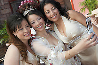 Bride taking self-portrait with two friends using mobile phone