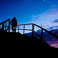 Kelimutu, Indonesia: la silhouette di un uomo percorre un sentiero a gradini prima dell'alba<br /> <br /> Kelimutu, Indonesia: silhouette of a man climbing up a stair before dawn. Smooth image and high ISO
